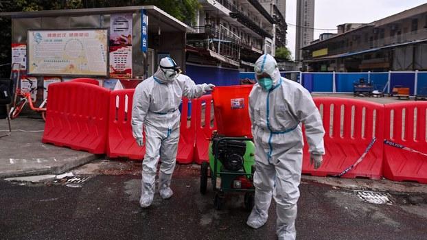 图为,2020年3月30日,身穿防护服的工人在湖北省武汉市的华南海鲜批发市场旁。(法新社)