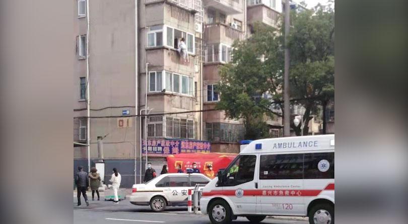 浙江嘉兴,一名隔离中的居民爬出窗外,消防员到场打开气垫。(志愿者提供/记者乔龙)