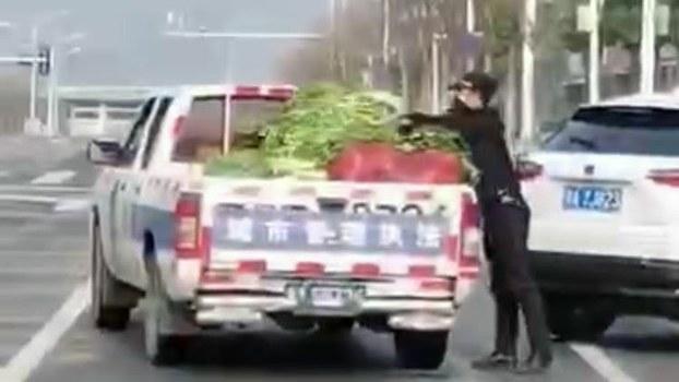 武汉城管将四川救灾物资蔬菜,往城管车上放。(视频截图)