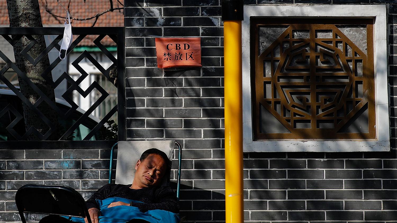 """虽然武汉城疫情未解除,但四川和安徽两个省政府却忙着""""摘口罩""""。图为,2020年3月11日,一名男子的口罩挂在北京中央商务区的树枝上。(美联社)"""