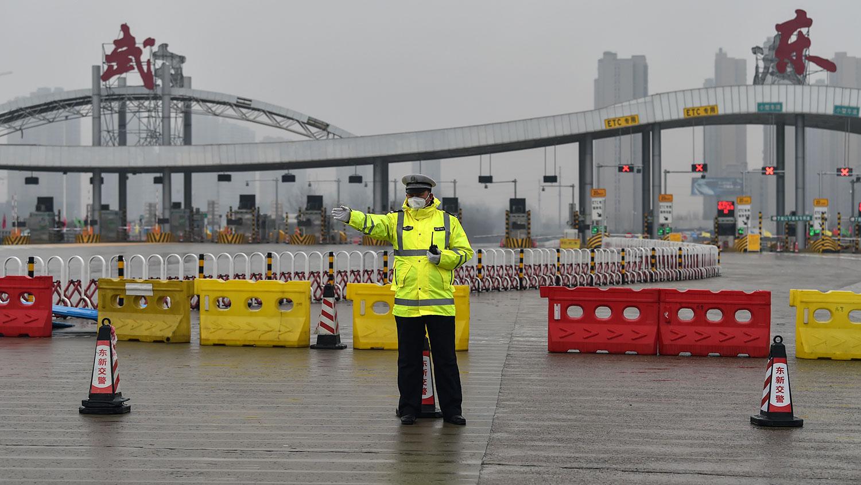 图为,2020年1月25日,武汉市肺炎病毒爆发期间,一名警官在警方封锁的一条道路前示意,限制人们离开湖北省武汉市。(法新社)
