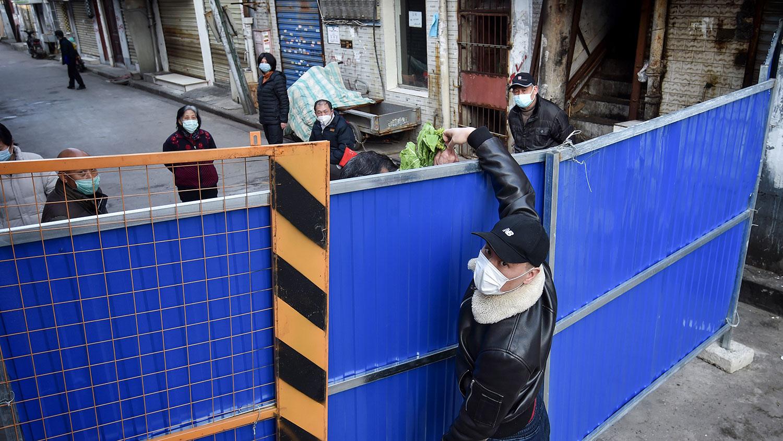 图为,2020年2月23日,在湖北省武汉市,一名男子正在向障碍物另一侧的人运送蔬菜,以阻止其他人进入。(法新社)