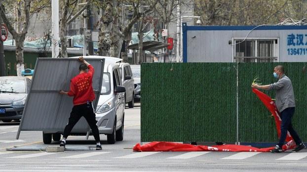 图为,2020年3月21日,工人消除了武汉街道上的障碍。(路透社)