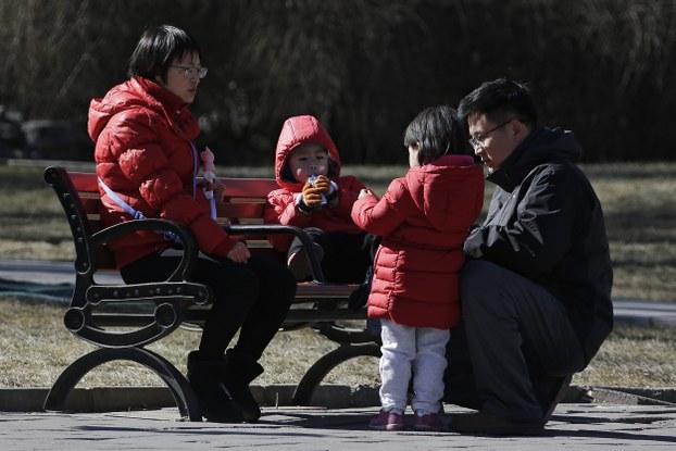 中国一对夫妇在北京的一个公园里陪孩子玩耍。(美联社)