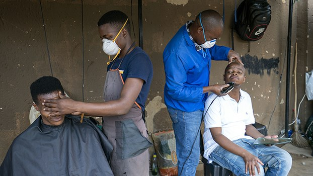 新冠疫情在非洲蔓延。图为南非理发师3月25日戴着口罩为顾客服务。(美联社)