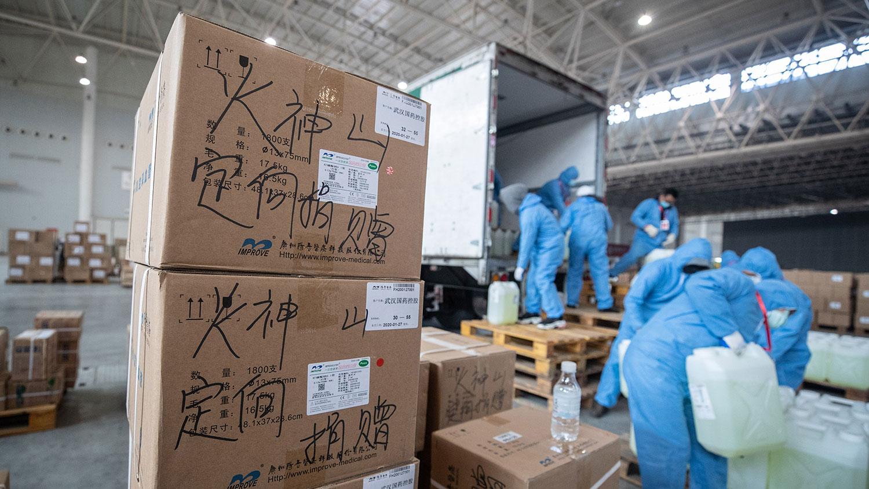 2020年2月4日,工作人员和志愿者在武汉市会展中心的仓库搬运医疗用品,该中心改建为临时医院。(法新社)