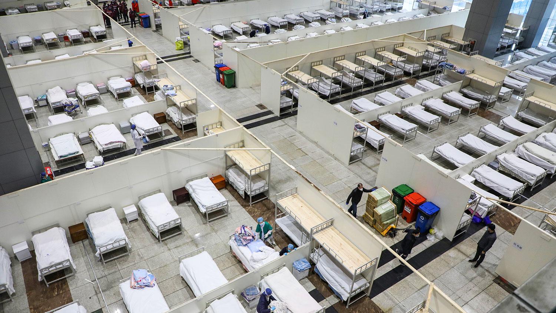 2020年2月5日,医务人员和工人准备收拾床铺,在武汉市会展中心改建为临时医院,接收轻度新型冠状病毒感染患者。(法新社)