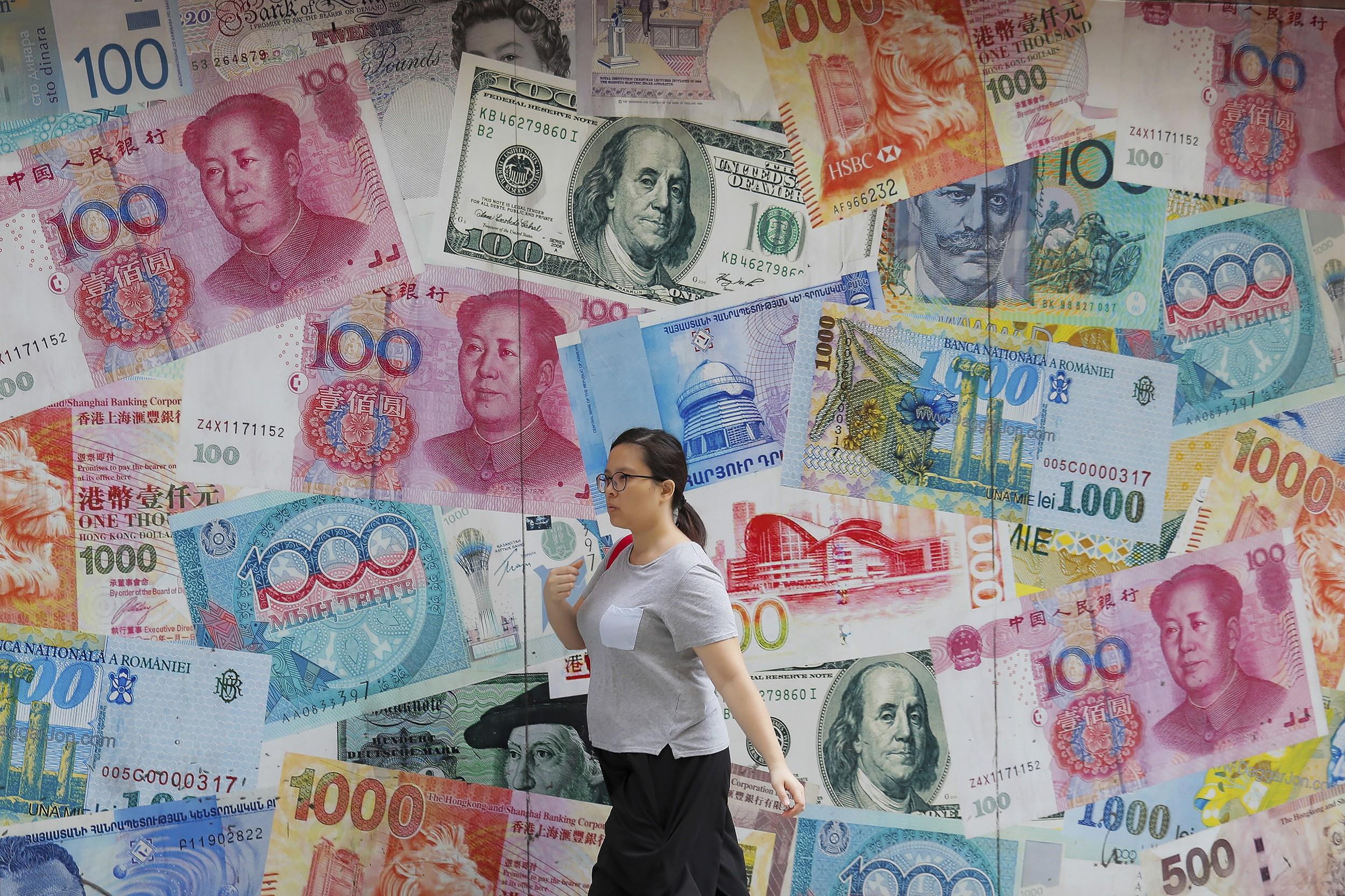 一名女子走过香港街头贴满人民币和美金的广告牌前。(美联社)