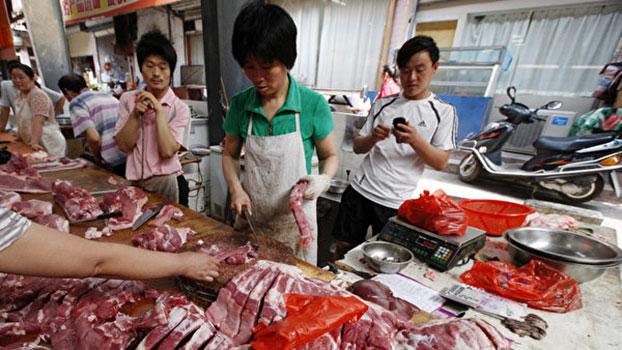 贸易战影响中国股市、楼市等消费品领域,其中末端消费者受到的伤害最大,民众基本生活用品近期也出现价格急升的现象,蔬菜、水果、肉类涨价的幅度都非常大。图为安徽淮北某市场,市民们在选购猪肉。(AFP)