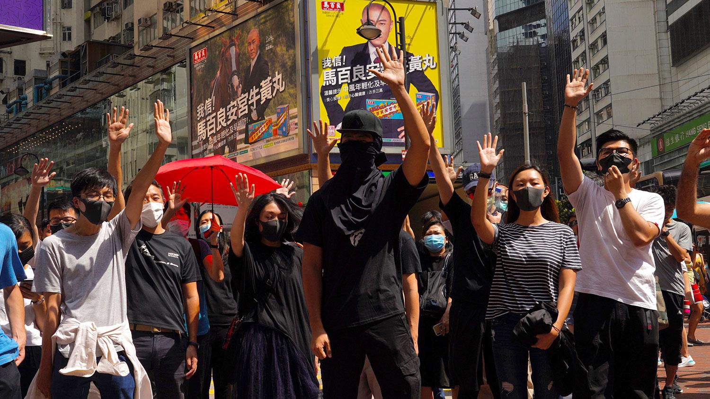 2019年10月4日,香港抗议者戴着口罩并举起张开手掌的单手,代表五大诉求。(美联社)
