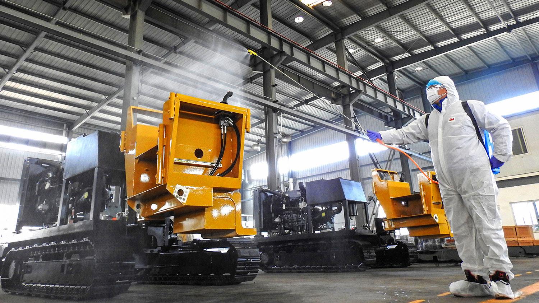 图为,2020年2月9日,江苏省连云港一家工厂恢复工作之前,工人实施防疫消毒。(法新社)