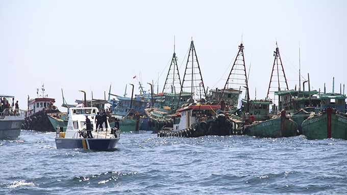 资料图片:2019年5月4日,印尼海洋渔业部的一艘巡逻艇经过因非法捕鱼而被扣留的外国渔船。(美联社)