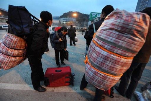 资料图片:2009年1月8日,几位农民工在贵州省的一个火车站附近收拾行李。(法新社)