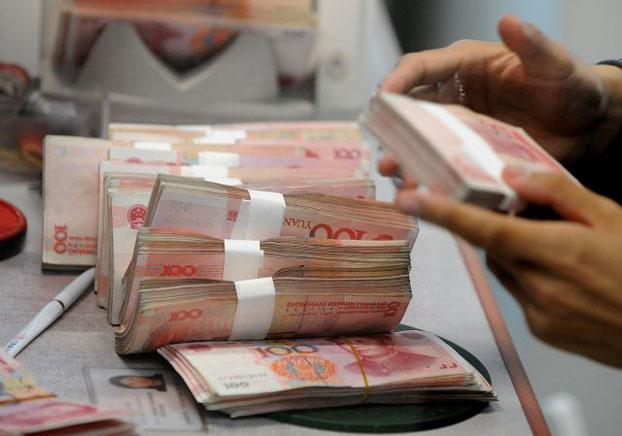 资料图片:中国的一位银行工作人员在清点人民币。(法新社)