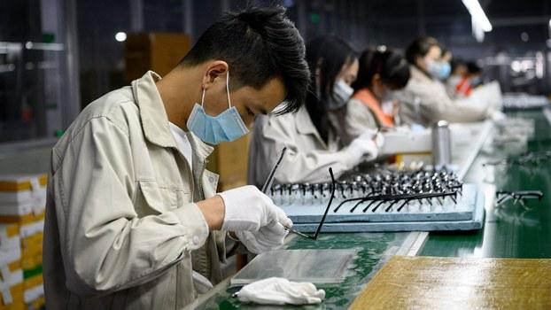 受疫情影响,2月份中国制造业采购经理指数(PMI)为35.7%,比上月下降14.3个百分点。图为2020年2月28日在温州一家眼镜公司,工人戴着口罩抛光眼镜架。(法新社)