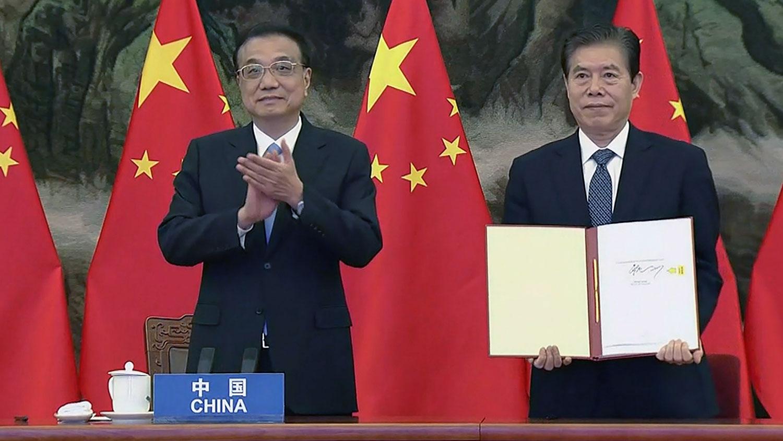 2020年11月15日,中国总理李克强(左)和中国商务部长钟山代表(右)在区域全面经济合作伙伴关系(RCEP)签字仪式上东盟峰会上签署贸易协定。(AFP)