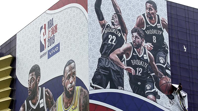一座体育馆外关于美国NBA上海赛2019的广告板,一名工人正在将其摘下。(美联社)