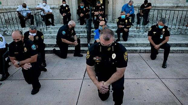 """2020年5月30日,美国佛罗里达州迈阿密戴德郡珊瑚墙市(Coral Gables)警察以""""单膝跪地""""的方式声援示威者。(法新社)"""