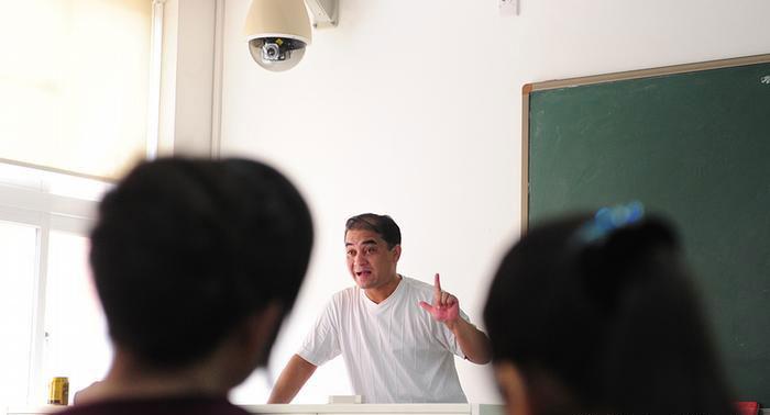维吾尔族学者伊力哈木在摄像头下上课。(AFP)