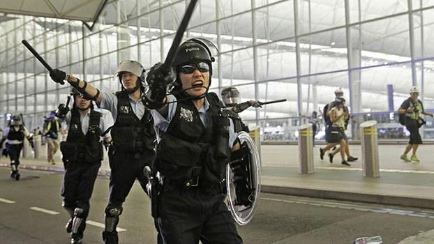 2019年8月13日,警察手持警棍在香港机场对民众喊话。(美联社)
