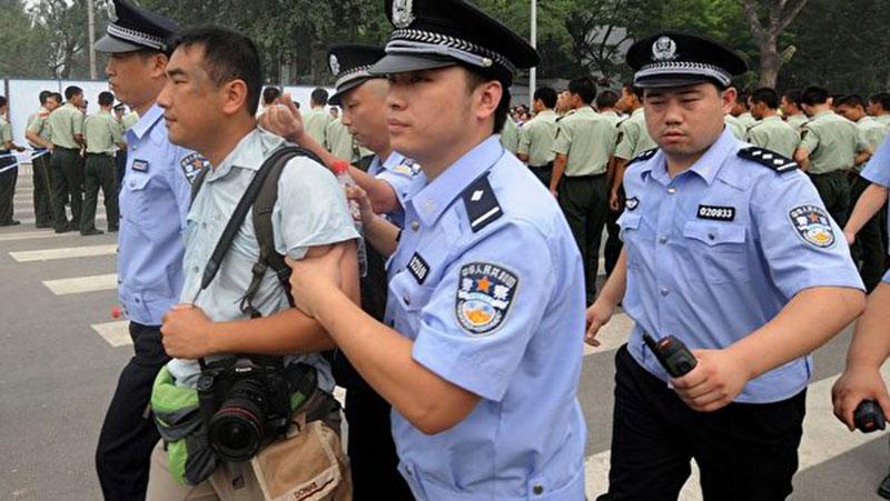 2008年7月25日,香港多家媒体采访北京开售奥运门票的混乱情况时,多名记者被公安粗暴对待,图为《南华早报》摄影记者被数名公安押带。(AFP)