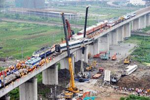 图片:7月23日,在温州甬温线铁路上,一列北京开往福州与杭州开往福州的动车,发生追尾事故,导致四节车厢坠落高架桥下,官方公布数据,称此次事故40人死亡,192人受伤。(法新社)