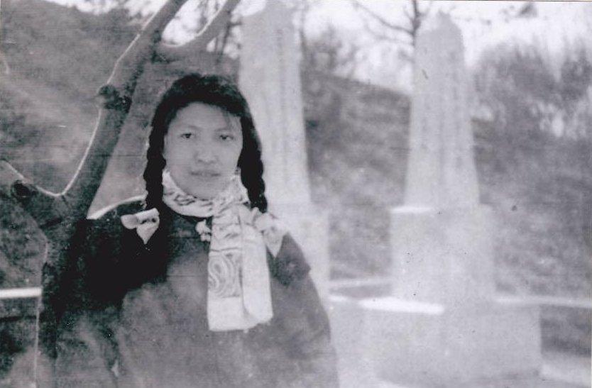 """1959年,林昭在北京陶然亭,背景是高君宇及其女友石评梅的墓碑。高君宇墓碑侧面刻有一首海涅的诗:""""我是宝剑,我是火花,我愿生如闪电之耀亮,我愿死如彗星之迅忽。""""(图源:维基百科/连曦的林昭文集)"""