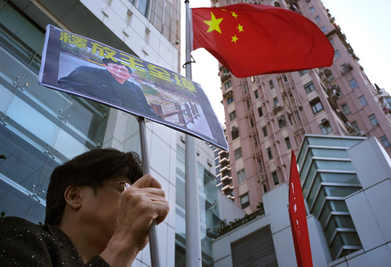 """2019年1月29日,中国政府驻香港联络处中联办外,一名示威者拿着""""释放王全璋""""的图片。(AP)"""