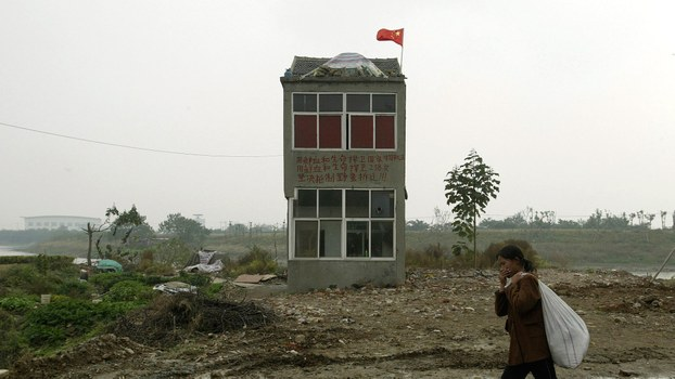 资料图片:江苏省南京市郊区,一名妇女走过了这地区的最后一所钉子房。(路透社)