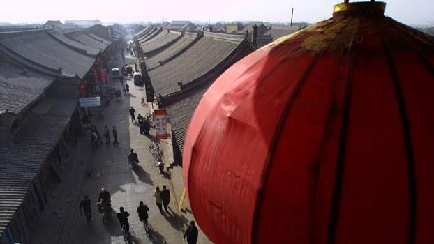 资料图片:一盏灯笼悬挂在俯瞰山西省平遥古城的塔上。(路透社)