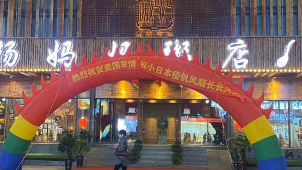 """中国沈阳的一家""""杨妈妈粥店""""挂出的庆祝美国日本疫情横幅(Public Domain)"""