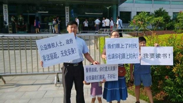 深圳春风劳动争议服务部负责人张治儒(左)被捕前带领家人在街头抗议(Public Domain)