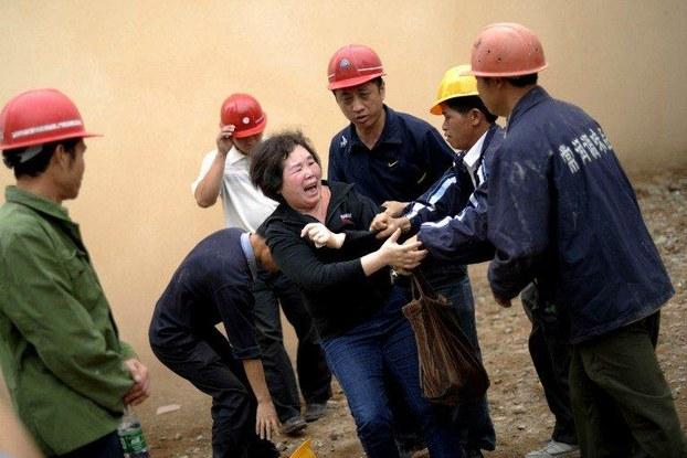 图片: 一名拆迁户试图保护其房屋免受暴力拆迁,与拆迁人员发生推撞。 (法新社资料图片)
