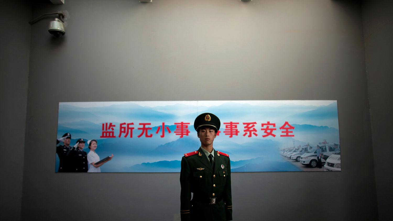 """据""""全国人大""""微信号称,近年来,低龄未成年人实施严重犯罪的案件时有发生,引发社会关注。图为警察在北京第二拘留中心入口处的监控摄像头下站岗。(美联社)"""