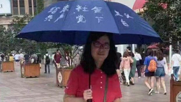 """张展在上海南京东路步行街举伞,促结束""""社会主义,共产党下台""""。(志愿者提供/记者乔龙)"""