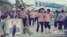图片:近千名村民打着横幅堵路抗议,还有村民将一副毛泽东画像摆在横幅下。(微博图片)