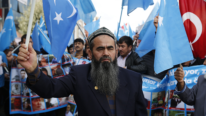 """资料图片:流亡土耳其的维吾尔人在伊斯坦布尔手举""""东突厥斯坦""""旗帜抗议中国的新疆政策(美联社)"""