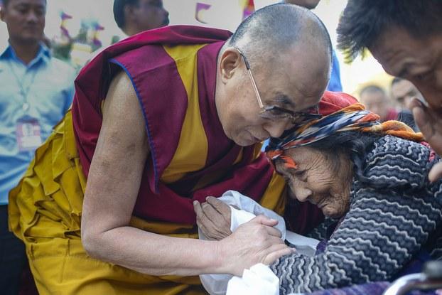 图片:达赖喇嘛在印度南部孟戈德西藏甘丹寺传法时向年迈藏人表达慰问。(达赖喇嘛网站)