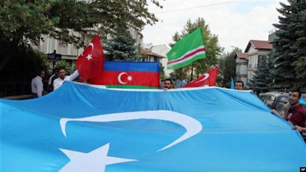 资料图片:旅居土耳其的维吾尔人手举东突厥斯坦旗帜在中国驻土耳其使馆前示威(美联社)