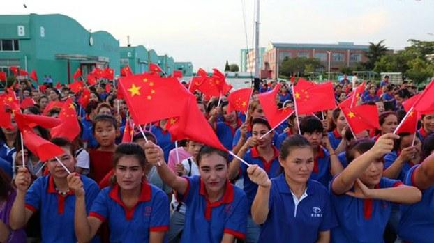 中国青岛泰光制鞋公司为美国企业耐克的全球最大代工厂之一,这里有数百名维吾尔年轻女性劳工,她们在此受到严密监控和洗脑教育。图为这些维吾尔女工参加中共建政庆祝。(中国民族宗教网/2019年10月)