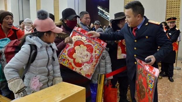 """铁路工作人员在西藏拉萨火车站派发写有""""福""""字的中国新年礼物。(法新社/新华社)"""