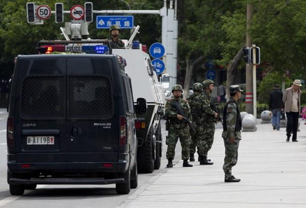 中国国防白皮书披露,武警部队2014年以来协助新疆打掉近1600个暴恐团伙,抓捕暴恐人员近13000人。图为新疆乌鲁木齐人民广场附近的入口布置了装甲车和武装警察。(美联社)