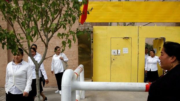 新疆当局被关闭的再教育营被还原成学校、妇幼保健院等,有些转移到地下继续运作。图为,新疆维吾尔自治区喀什,维吾尔族妇女离开再教育中心。(路透社)