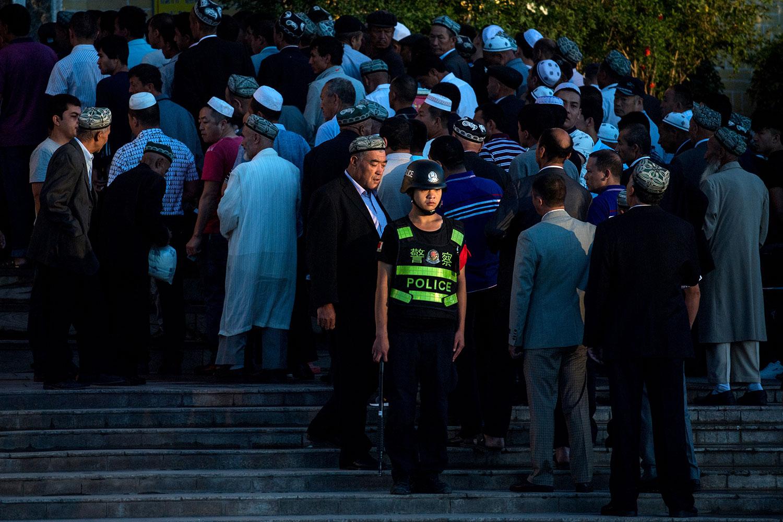 资料图片:2017年6月26日,一名警察站岗,穆斯林在新疆维吾尔自治区喀什清真寺开斋节早晨祈祷。(法新社)