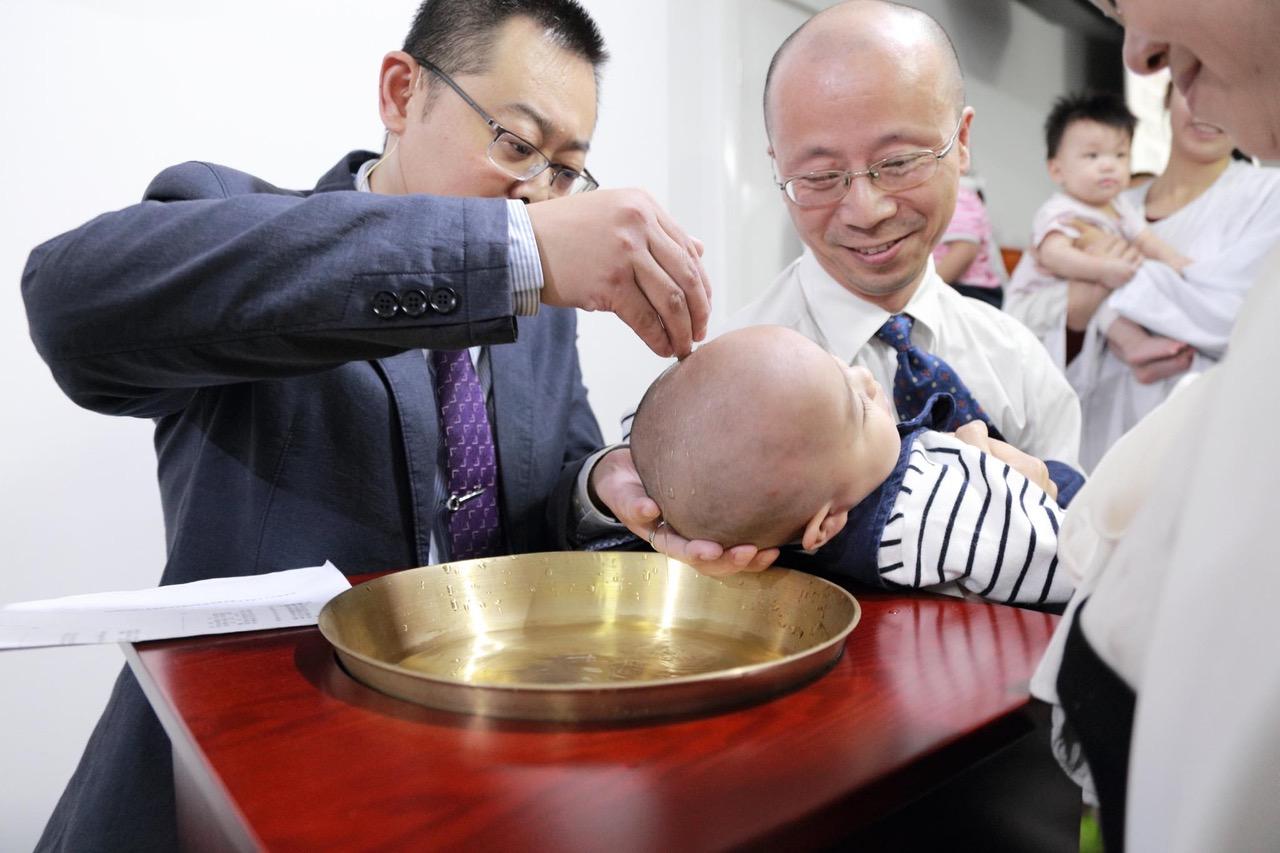秋雨教会被关押中的王怡牧师(左)过去为小文施洗。(廖强提供)