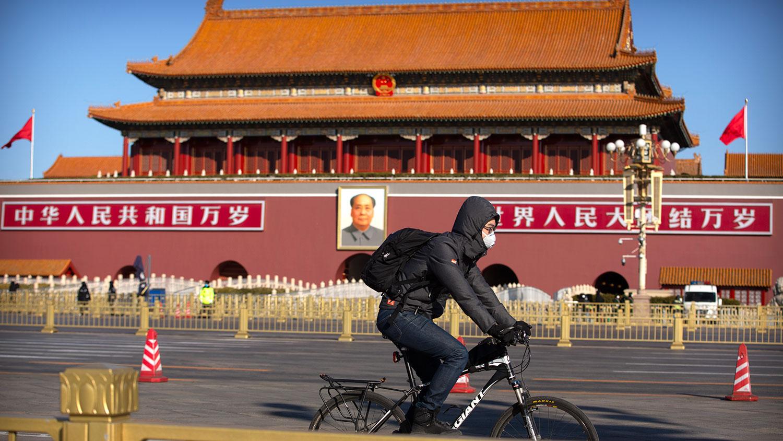 2020年2月4日,一名男子戴着口罩骑自行车经过北京天安门。(美联社)
