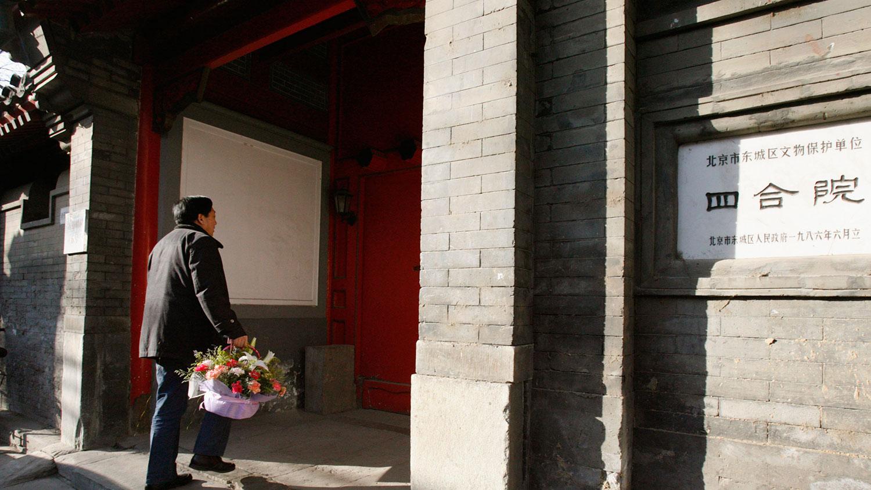 资料图片:2007年1月17日,来访者携鲜花进入已故中共中央总书记赵紫阳的北京四合院。(路透社)