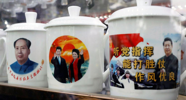 """资料图片:北京一家商店展示的带有中国国家主席习近平形象的纪念品水杯,一个杯子上有口号""""听党指挥,能打胜仗,作风优良""""。(路透社)"""
