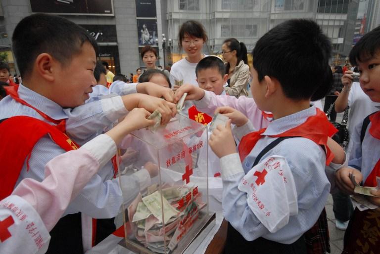 图片: 中国国务院日前推出新文件,规定以诽谤造谣损害慈善组织将受到法律严肃追究。图为在世界红十字日,将压岁钱捐给红十字会的小学生。 (法新社资料图片)