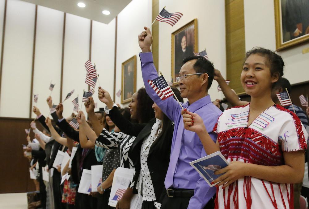 资料图片:一位亚裔女孩与其他人一起在入籍仪式上挥舞国旗。(美联社)